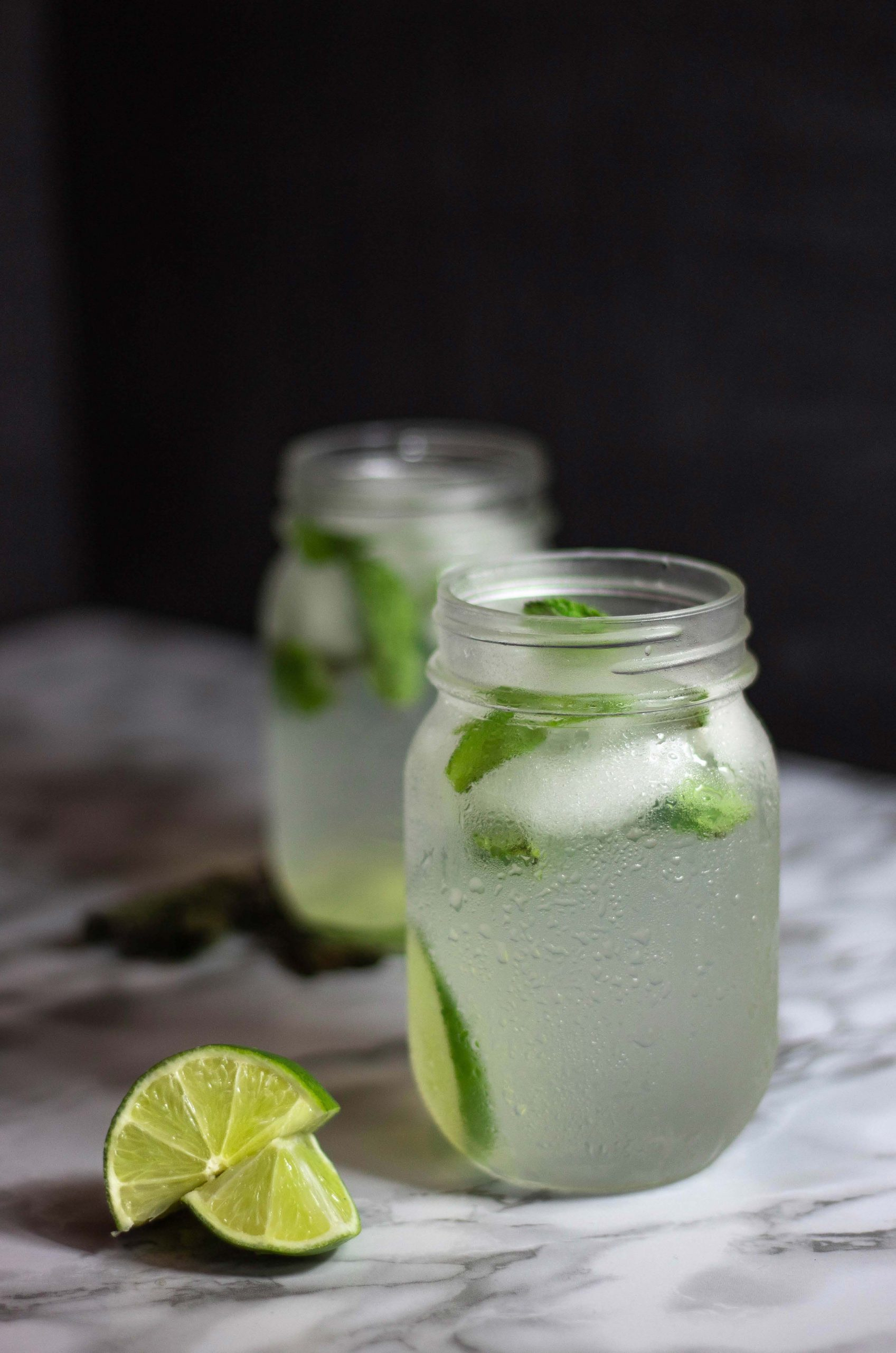 Two glasses of clear beverage garnished with mint and limes