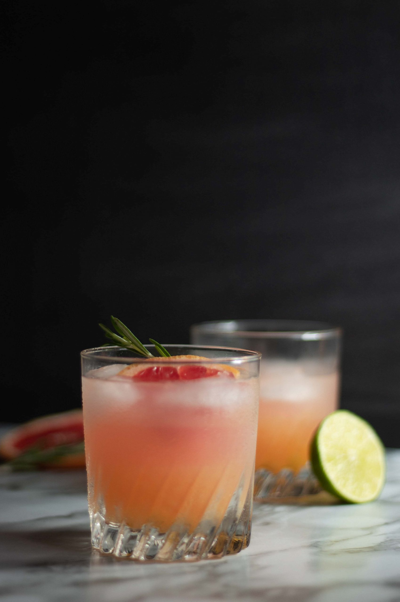 Two glasses of an ombre alcoholic drink with garnish