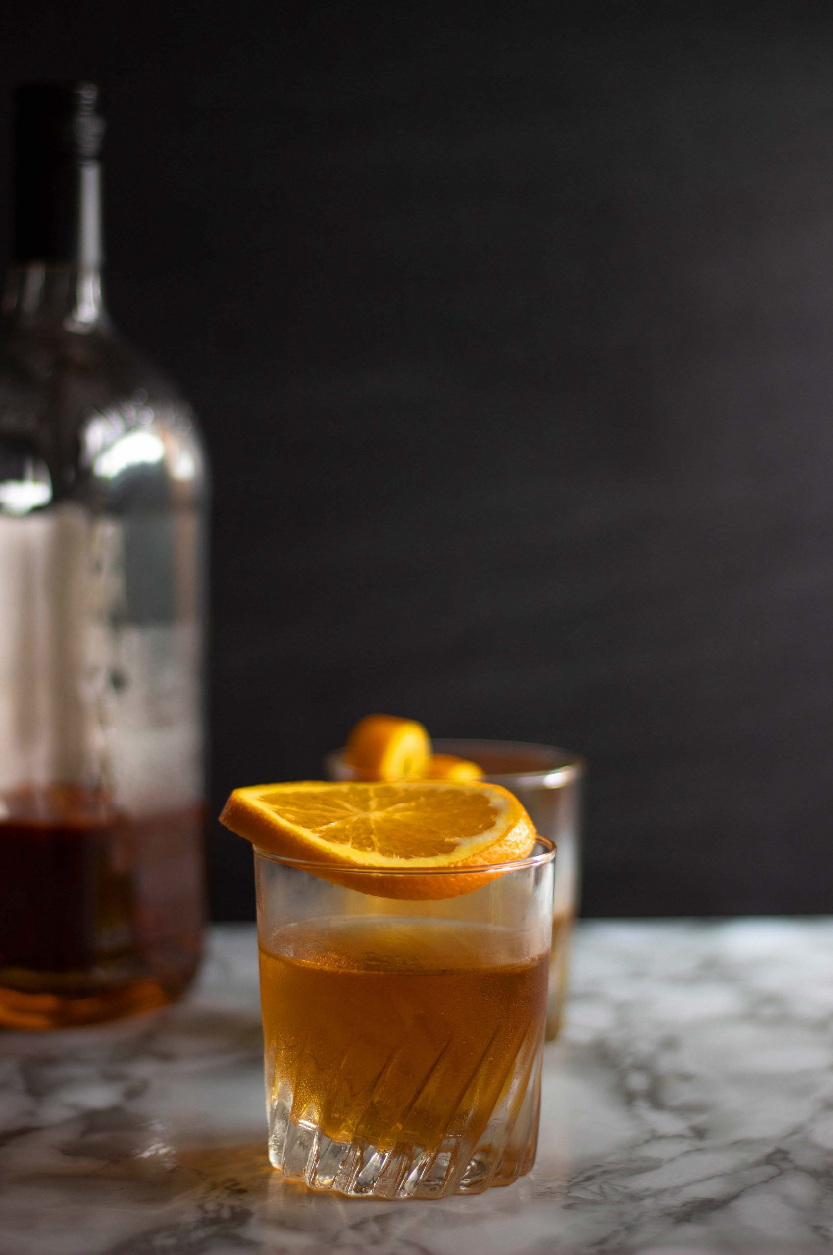A chilled glass of an Old Fashioned with an orange slice